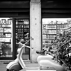 Milan, Italy - April 7, 2012: A parked Lambretta stands in front of one of the typical grocery shops in the historical center of Milan. Black and White image.