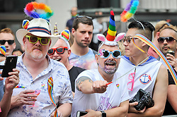 © Licensed to London News Pictures. 08/07/2017. London, UK. Men wearing colourful headgear in the crowd.  Tens of thousands of visitors, many wearing eye-catching costumes, gather to watch and take part in the annual Pride in London Parade, the largest celebration of the LGBT+ community in the UK.   Photo credit : Stephen Chung/LNP