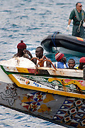 "Tenerife / Los Cristianos June 7, 2006 - A fishing boat called ""Cayucos"" by the inhabitants of the island, with 85 would-be immigrants from West Africa intercepted by Spanish police of the coast of Tenerife in the Canary Islands are seen in an open wooden fishing vessel as they approach the port of Los Cristianos. They arrived on June, carrying 85 would-be immigrants, in the archipelago which has received more than 7,000 Africans so far this year, more than half to the tourist resort island of Tenerife. At least 1,000 more are believed to have died trying to make the sea crossing, mostly in small fishing boats"