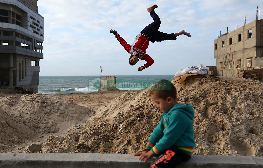 January 2, 2018 - Gaza, Palestinian Territories, Palestine - A Palestinian boy jumps over sand on the beachfront of the al-Shati refugee camp, in Gaza City. (Credit Image: © Majdi Fathi/NurPhoto via ZUMA Press)