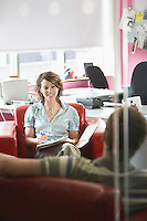 Two office workers sitting on sofas in office elevated view focus on woman