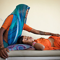 An ASHA (local female health advisor) tends to Mukhi, age 22 (in orange), pregnant with her third child (her previous two children died before reaching their first birthdays) at the Satanwarda Community Health centre. Mukhi was at the health centre for a consultation with the ANM. ASHAs provide a free referral service to local women, keeping them in touch with government health services. For this ASHA's receive a fee from the government for every referral. This is one means by which the government and partners UNICEF are increasing the rate of institutional deliveries in Madhya Pradesh state. ..Shivpuri district in Madhya Pradesh suffers from poor health outcomes. Of particular concern is the high rate of maternal mortality. One of the Indian government's aims, with partners Unicef, is to encourage the population to adopt practices to improve sanitation and health practices. In an area made up of traditionally disadvantage groups and suffering low literacy rates, this can be a challenge. ..A survey found that radio was the most readily accessible media by the Shivpuri community with more than half saying they tuned in several times a day. ..Dharkan 107.8 FM will go on air in July. The station that will broadcast to 75 villages in a 15-kilometer radius reaching 170,000 people...Rather than preaching educational messages, the station, which is already producing pilot programs, uses humor and folk artists performing in the local language to entertain and inform their audiences. There is a major impact, especially on women, who are contributing their voices to such wide-ranging issues as caste discrimination, female feticide and women,A?o?s empowerment. ..Photo: Tom Pietrasik.Shivpuri, Madhya Pradeh. India.June 2009
