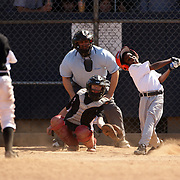 A young baseball player swings and misses a pitch while batting during the Norwalk Little League baseball competition at Broad River Fields,  Norwalk, Connecticut. USA. Photo Tim Clayton