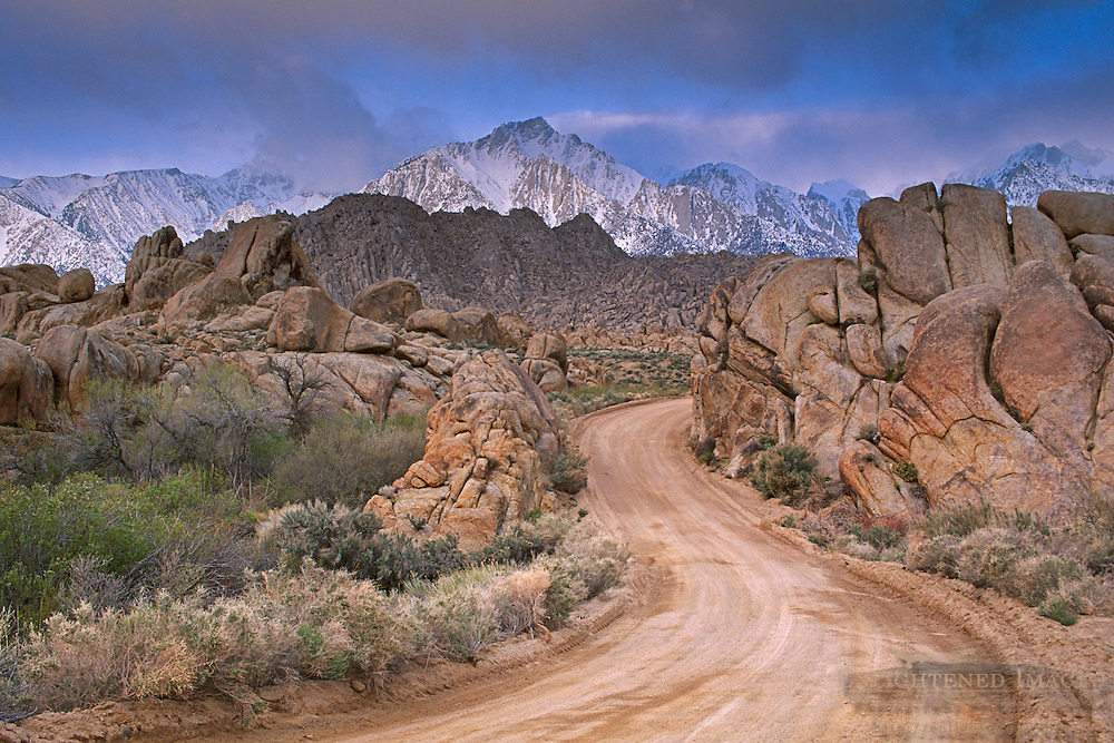 Twisting dirt road below mountain peak during a spring snow storm, Alabama Hills, Eastern Sierra, Lone Pine, California