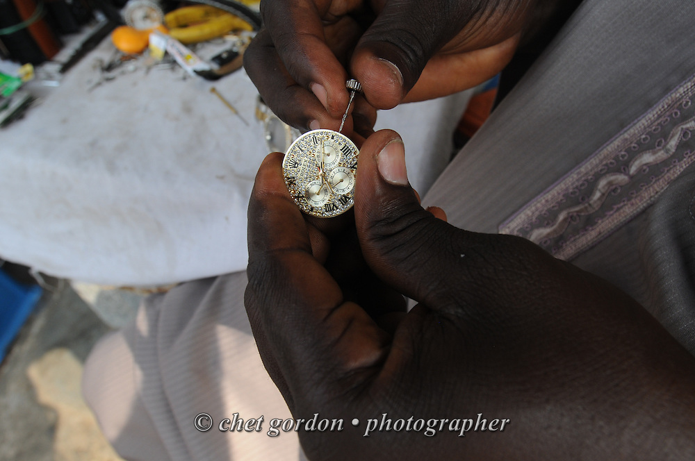 A Nigerian watch repairman works on a watch at his stand at the Wuse Market in Abuja, Nigeria on Saturday, December 8, 2012.