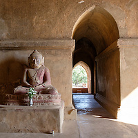 A seated Buddha with flower offerings inside one of the vestibules of the Dhammayangyi Temple in Bagan, Myanmar (Burma).
