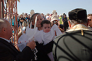 Israel, Jordan River, Near Jericho, Qasr al Yahud. An Orthodox Christian priest Baptising a baby at the baptismal site of Qasr al Yahud in the Jordan River January 18th 2008. Epiphany, the day of Jesus? baptism, when ?the heavens opened, and he saw the spirit of God descending like a dove and lighting on him.? Celebrated in January by the Greek Orthodox Church. The holy day transforms the area as thousands of pilgrims flock to what is one of the most sacred and least visited places in Israel.