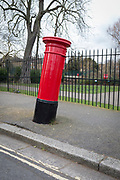 A leaning Royal Mail pillar box stands near a leaning tree in Sunray Gardens, on 26th February 2018, in south London, England.