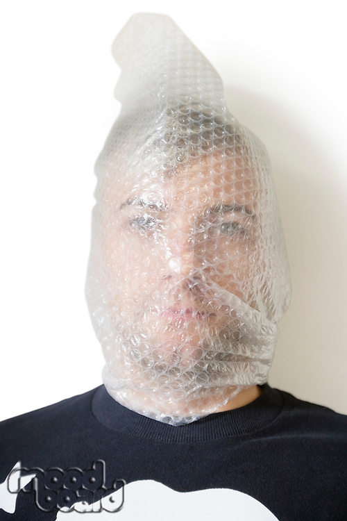 Portrait of man wrapped in bubble wrap