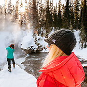 Clients explore along a waterfall at sunrise in Yellowstone National Park.