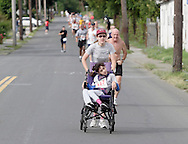 Middletown, New York - A woman pushing a girl in a wheelchair competes in the Run4Downtown four-mile road race on Aug. 21, 2010.