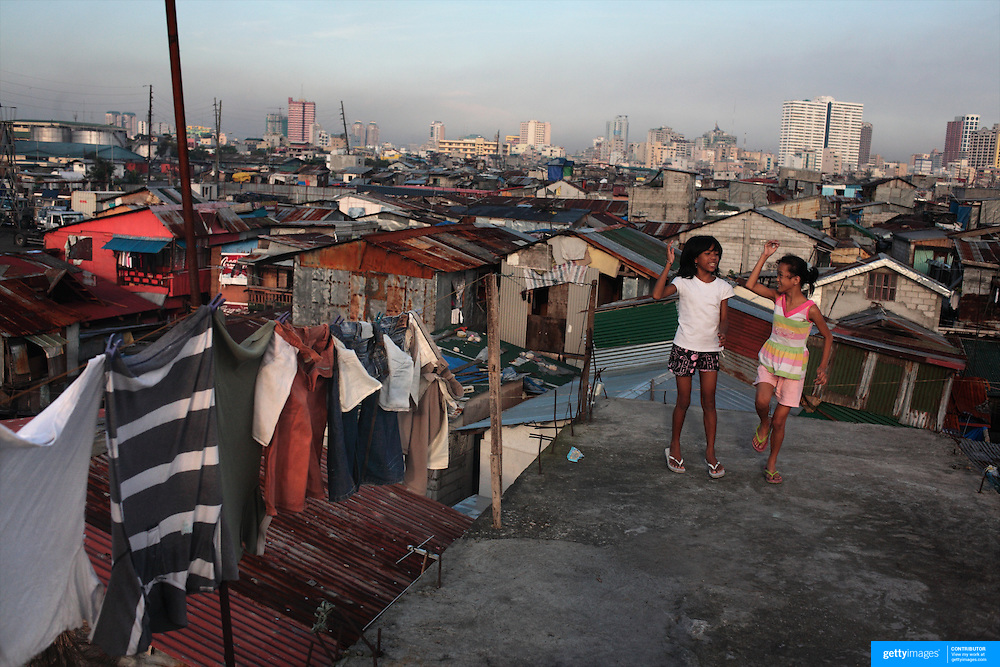 Two young girls, Vicky Valdez, 12, (left) and Pinky Penaranda, 11, sing the latest pop hits as they dance on the roof tops in the Parola district of Tondo, one of the worst slum areas of Manila on October 8, 2008 in Manila, the Philippines. Photo Tim Clayton