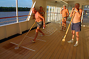 The Amazonas, the World's largest body of fresh water, passes by as passengers of the MS Europa play shuffleboard.