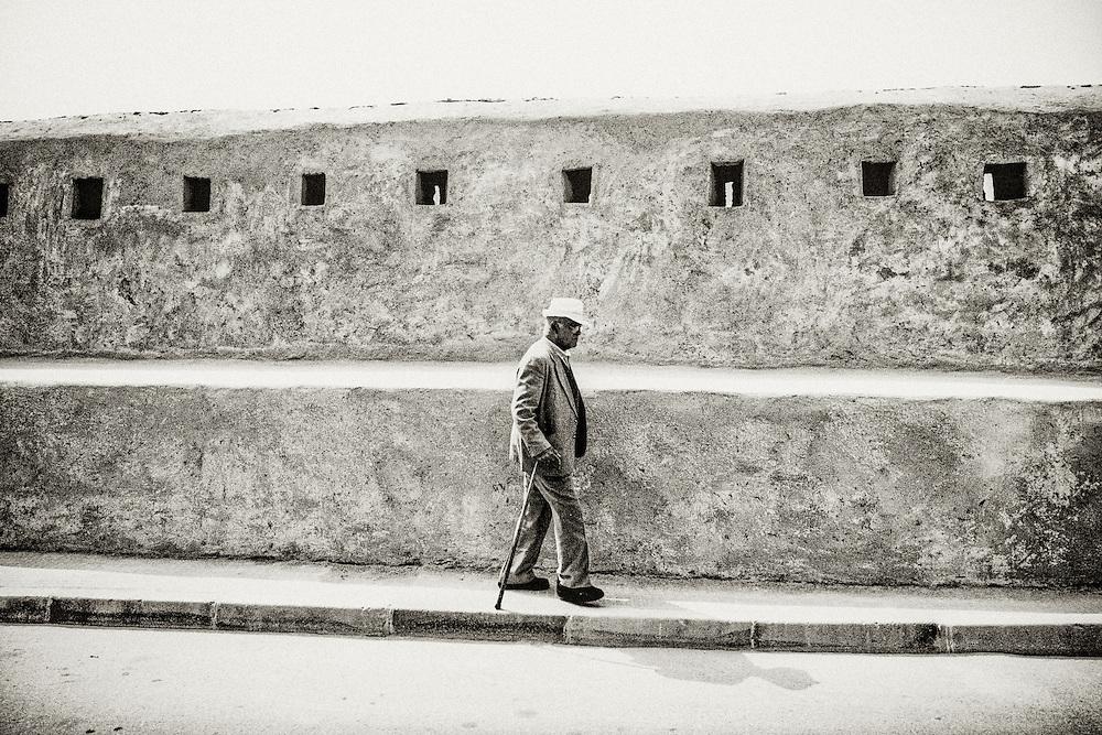 198 / Sale Stadtmauer: AFRIKA, MAR, MAROKKO, SALE, Maerz 2010: Ein alter Mann laeuft mit Gehstock entlang der Stadtmauer von Sale. Sale ist die Nachbarstadt von Rabat am noerdlichen Ufer des Bou-Regreg an der Atlantikkueste von Marokko. - Marco del Pra / imagetrust - Stichworte: Afrika, Marokko, Maghreb, Maroc, Sale, Rabat, Medina, Altstadt, Koenigreich, Koenig, Mohammed VI,  Schwarz, Weiss, Mauer, Stadtmauer, Festung, Gehstock, alt, alter, Mann, Hut, Strasse, Buergersteig, Gehweg, Spazierstock, Loch, Loecher,