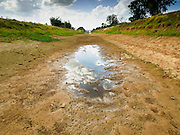 01 JULY 2015 - NON PHAK NAK, SUPHAN BURI, THAILAND:  A puddle in the bottom of an empty irrigation canal in Lopburi province. Normally, the canal is completely full at this time of year. Central Thailand is contending with drought. By one estimate, about 80 percent of Thailand's agricultural land is in drought like conditions and farmers have been told to stop planting new acreage of rice, the area's principal cash crop. Water in reservoirs are below 10 percent of their capacity, a record low. Water in some reservoirs is so low, water no longer flows through the slipways and instead has to be pumped out of the reservoir into irrigation canals. Farmers who have planted their rice crops are pumping water out of the irrigation canals in effort to save their crops. Homes have collapsed in some communities on the Chao Phraya River, the main water source for central Thailand, because water levels are so low the now exposed embankment is collapsing. This is normally the start of the rainy season, but so far there hasn't been any significant rain.    PHOTO BY JACK KURTZ