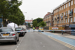© Licensed to London News Pictures. 02/06/2018. London, UK.  Police at the crime scene cordon in Cable Street, east London this morning. Police were called to Cable Street E1 at 17:56 on Friday 1st June to reports of a stabbing. A 22 year old male suffering from multiple stab wounds was taken to an east London hospital in a critical condition. The victim remains in a critical condition this morning.  Photo credit: Vickie Flores/LNP