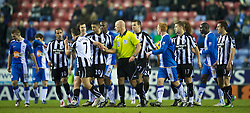 WIGAN, ENGLAND - Sunday, January 2, 2011: Newcastle United's Joey Barton is chased by Wigan Athletic players and referee Howard Webb after a two-footed tackle during the Premiership match at the JJB Stadium. (Pic by: David Rawcliffe/Propaganda)