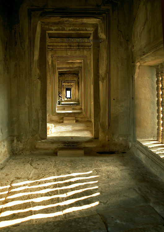 Angkor Wat: view along a corridor  of one of its galleries.Parallel linear pattern of sunlight and shadow projected through balustraded window opening.  Successive doorways recede into the distance.