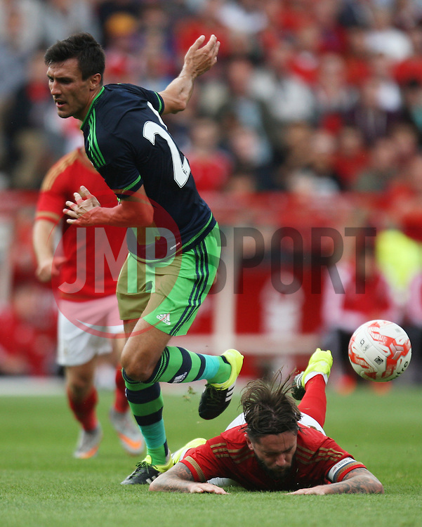 Henri Lansbury of Nottingham Forest (R) is fouled by Jack Cork of Swansea City<br /> <br />  - Mandatory by-line: Jack Phillips/JMP - 25/07/2015 - SPORT - FOOTBALL - Nottingham - The City Ground - Nottingham Forest v Swansea - Pre-Season Friendly