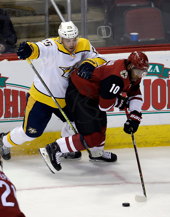 Arizona Coyotes left wing Anthony Duclair (10) shields the puck from Nashville Predators defenseman Alexei Emelin in the second period during an NHL hockey game, Thursday, Jan. 4, 2018, in Glendale, Ariz. (AP Photo/Rick Scuteri)