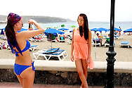 Two young girls relax on the beach promenade and take pictures of each other.