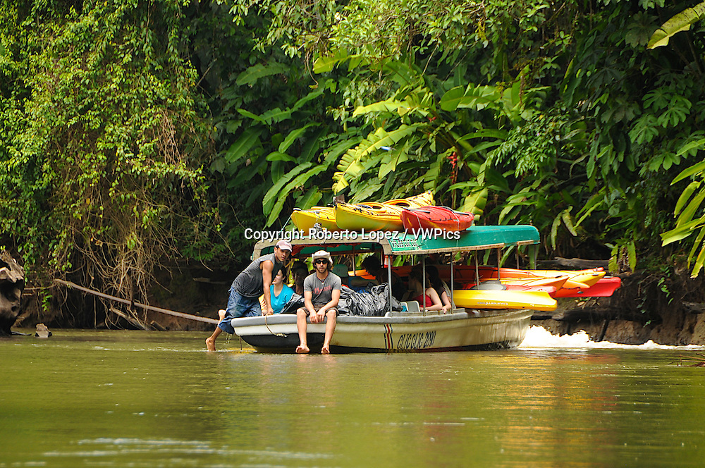 Group of people going kayaking on a local boat at the Tortuguero River, Limon, Costa Rica