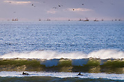 The fishing fleet of Monterey operates in the bay at sunset on a stormy May evening, while surfers paddle out for a sunset surf session.