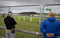 © Licensed to London News Pictures. 04/07/2020. Epsom, UK. Two race goes stand outside a security fence as riders in The Investec Surrey Stakes Derby Day race pass Tattenham Corner. Today's race meeting is being held behind closed doors due to the coronavirus lockdown rules. Seven races are being held in one day including The Oaks, with The Derby being run at 4:55pm. Photo credit: Peter Macdiarmid/LNP