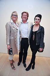THEO & LOUISE FENNELL and their daughter COCO FENNELL at an exhibition of photographic portraits by Bryan Adams entitled 'Hear The World' at The Saatchi Gallery, King's Road, London on 21st July 2009.