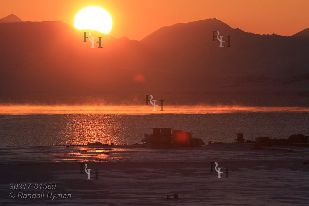 Midnight sun skims along horizon at start of endless summer sunlight in April at the international science village of Ny-Alesund on Spitsbergen island in Kongsfjorden; Svalbard, Norway.