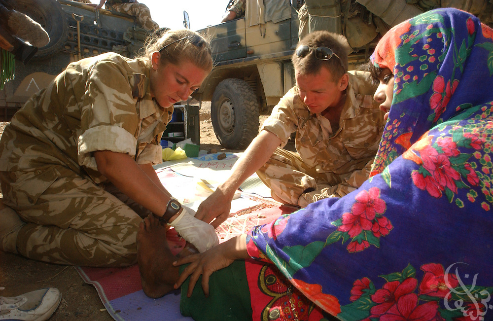 British field medic Corp. Cerianne Brown (l) and her team treat local Afghan children June 21, 2002 during a humanitarian aid visit to the village of Dandar in Central Afghanistan. Britain announced the day before that it will withdraw the majority of its forces beginning the first week of July.
