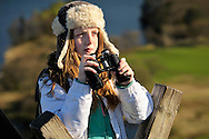 Girl hiker with fur hat and binoculars on wooden stile on Loughrigg Fell above Windermere. Lake District National Park, UK