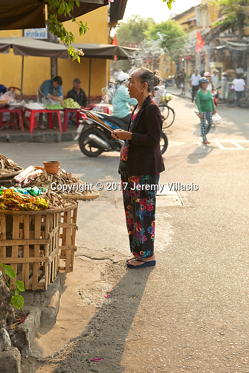 Elderly woman holding incense sticks and praying in the streets of Hoi An.