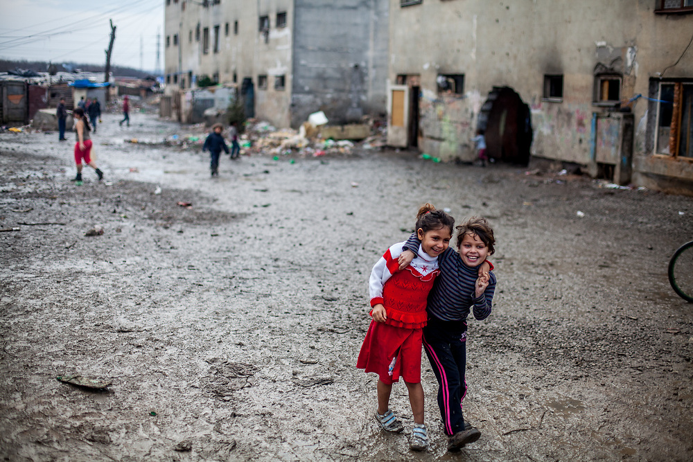 Two girls holding each other in front of a decrepit building at the Roma settlement in Moldava nad Bodvou (2015). From about 800 inhabitants of the segregated settlement 'Budulovska Street' are roughly 392 children up to the age of 16 years (2014) .