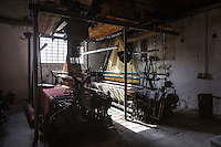 """SOVERIA MANNELLI, ITALY - 17 NOVEMBER 2016: A Jacquard mill (a power loom that simplifies  the process of making textiles) is seen here in the Lanificio Leo woolen mill in Soveria Mannelli, Italy, on November 17th 2016.<br /> <br /> Lanificio Leo was the first and last machine-operated woolen mill of Calabria, founded in 1873, it employed 50 people until the 1970s, when national policies to develop Italy's South cut out small businesses and encouraged larger productions or employment in the public administration.<br /> <br /> The woolen mill was on stand-by for about two decades, until Emilio Salvatore Leo, 41, started inviting international designers and artists to summer residencies in Soveria Mannelli. With their inspiration, he tried to envision a future for his mill and his town that was not of a museum of the past,<br /> Over the years, Mr. Leo transformed his family's industrial converter of Calabrian wool into a brand that makes design products for home and wear. His century old machines now weave wool from Australia or New Zealand, cashmere from Nepal and cotton from Egypt or South America. He calls it a """"start-up on scrap metals,"""" referring to the dozens of different looms that his family acquired over the years.<br /> <br /> Soveria Mannelli is a mountain-top village in the southern region of Calabria that counts 3,070 inhabitants. The town was a strategic outpost until the 1970s, when the main artery road from Naples area to Italy's south-western tip, Reggio Calabria went through the town. But once the government started building a motorway miles away, it was cut out from the fastest communications and from the most ambitious plans to develop Italy's South. Instead of despairing, residents benefited of the geographical disadvantage to keep away the mafia infiltrations, and started creating solid businesses thanks to its administrative stability, its forward-thinking mayors and a vibrant entrepreneurship numbering a national, medium-sized publishing house"""