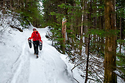 Carrying snowshoes up the trail to the John Muir Cabin, North of Juneau, Alaska, March 18, 2017. <br /> Photo by David Lienemann