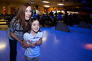 Jackie Harrigan and her daughter Megan Harrigan, 6, watch as Megans bowling ball rolls toward the pins during the bowling party held for Contestants in the Scripps Spelling Bee. Photo by: Ross Brinkerhoff.