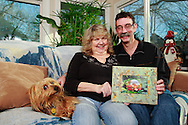 Patty and Jerry Woodbury with one of their photos in a frame they made in an art class, photographed at their home in Kettering, joined by thier dog Bondi, Saturday, December 22, 2012.