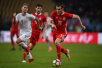 """Gareth Bale, right, of Wales national football team kicks the ball to make a pass against Guillermo Varela of Uruguay national football team in their final match during the 2018 Gree China Cup International Football Championship in Nanning city, south China's Guangxi Zhuang Autonomous Region, 26 March 2018.<br /> <br /> Edinson Cavani's goal in the second half helped Uruguay beat Wales to claim the title of the second edition of China Cup International Football Championship here on Monday (26 March 2018). """"It was a tough match. I'm very satisfied with the result and I think that we can even get better if we didn't suffer from jet lag or injuries. I think the result was very satisfactory,"""" said Uruguay coach Oscar Tabarez. Wales were buoyed by a 6-0 victory over China while Uruguay were fresh from a 2-0 win over the Czech Republic. Uruguay almost took a dream start just 3 minutes into the game as Luis Suarez's shot on Nahitan Nandez cross smacked the upright. Uruguay were dealt a blow on 8 minutes when Jose Gimenez was injured in a challenge and was replaced by Sebastian Coates. Inter Milan's midfielder Matias Vecino of Uruguay also fired at the edge of box from a looped pass but only saw his attempt whistle past the post. Suarez squandered a golden opportunity on 32 minutes when Ashley Williams's wayward backpass sent him clear, but the Barca hitman rattled the woodwork again with goalkeeper Wayne Hennessey well beaten."""