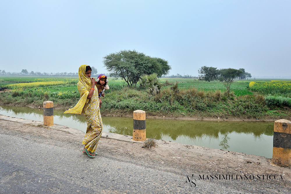 The road from Patna to Bodh Gaya.<br /> A woman with her child is going back to her village