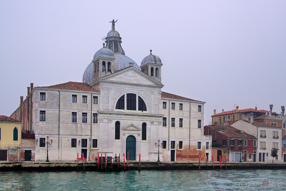 """Le Zitelle (officially Santa Maria della Presentazione) is one of the many parish churches in Venice. It is part of a former complex which gave shelter to young maidens (""""zitelle"""" in Italian) who had no dowry, and is located in the  Giudecca island. I took this picture from the water bus on the Giudecca Canal, on a misty evening of mid January."""