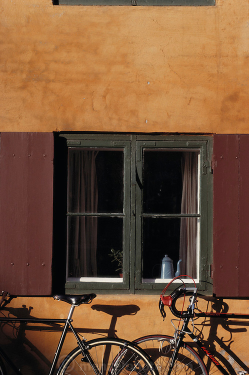 DEN_19_xs.Yellow row houses, Kronprinzessegade. Bicycles leaning against a wall with a shuttered window. Copenhagen, Denmark..