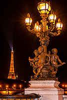 Art nouveau lamps adored with cherubs on the Pont Alexandre III bridge (the most ornate brige in Paris) with the Eiffel Tower in background, Paris, France.