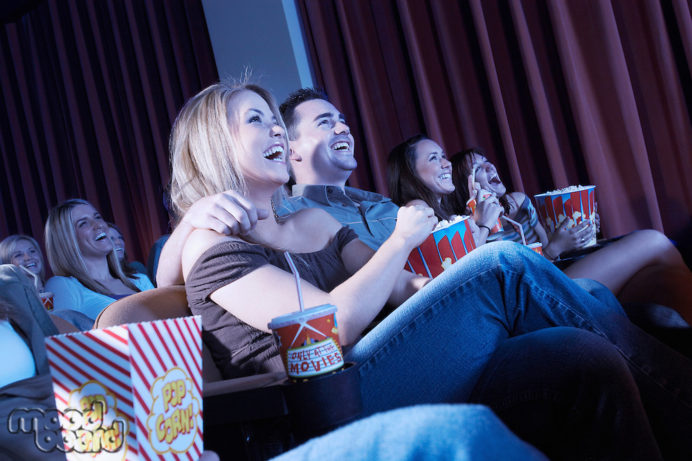 Smiling Couple sitting arms around Watching Movie in theatre
