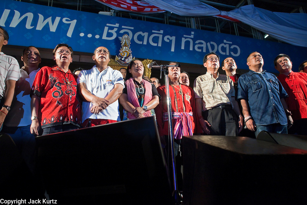 05 MAY 2010 - BANGKOK, THAILAND: Red Shirt leaders gather on their stage Wednesday night to honor Thai King Bhumibol Adulyadej during a ceremony to mark Thai Coronation Day Wednesday. The Red Shirts have been accused of being anti-monarchy and their Coronation Day Ceremony was a way of countering that perception. Coronation Day honors the day the King was officially crowned on May 5, 1950. Red Shirt protesters continued their actions in Bangkok Wednesday. The Red Shirts conditionally accepted the offer of Thai Prime Minister Abhisit Vejjajiva to dissolve parliament, investigate alleged human rights violations following the violence of April 10 and call for new elections in November of this year, 18 months earlier than they are currently scheduled. They are withholding final acceptance of the so called Road Map until the Prime Minister releases more specifics on the arrangement and announces the date for the dissolution of parliament. Proposals to amend the constitution are also a sticking point. The Red Shirts want the 1997 constitution reinstated, the government and other anti-Red Shirt groups want to keep the current constitution, enacted in 2007. The Red Shirts, who started their protest on March 13, continue to call for Thai Prime Minister Abhisit Vejjajiva to step down and dissolve parliament immediately and demand the return of ousted Prime Minister Thaksin Shinawatra.   PHOTO BY JACK KURTZ
