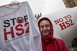 © licensed to London News Pictures. London, UK 16/07/2012. An 80 year-old protester posing with a sticker on his forehead as protesters demonstrating against the government's new high speed rail project outside the Houses of the Parliament. Photo credit: Tolga Akmen/LNP