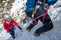 A close-up view on a female climbers ascending snow couloir of Aiguilles Marbrées.