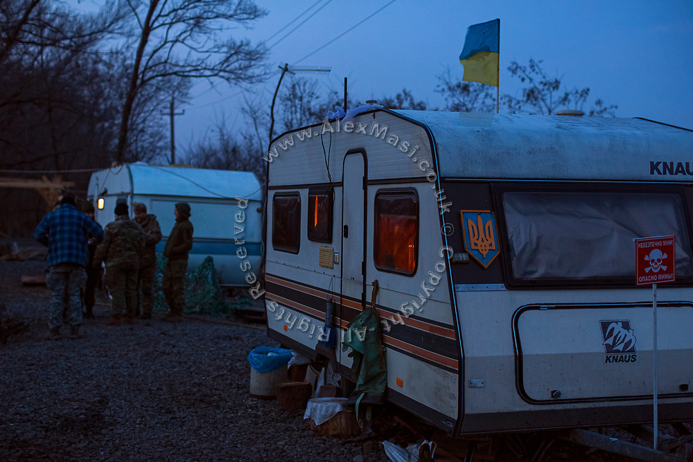 In the evening, members of ASAP are talking outside of their caravans, set up at the Mayorsk base near the frontline in eastern Ukraine.