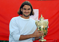 Mens Singles Champions Roger Federer holds the Trophy in front of a Swiss flag. Wimbledon Tennis Championship, Day 13, 6/07/2003. Credit: Colorsport / Matthew Impey DIGITAL FILE ONLY