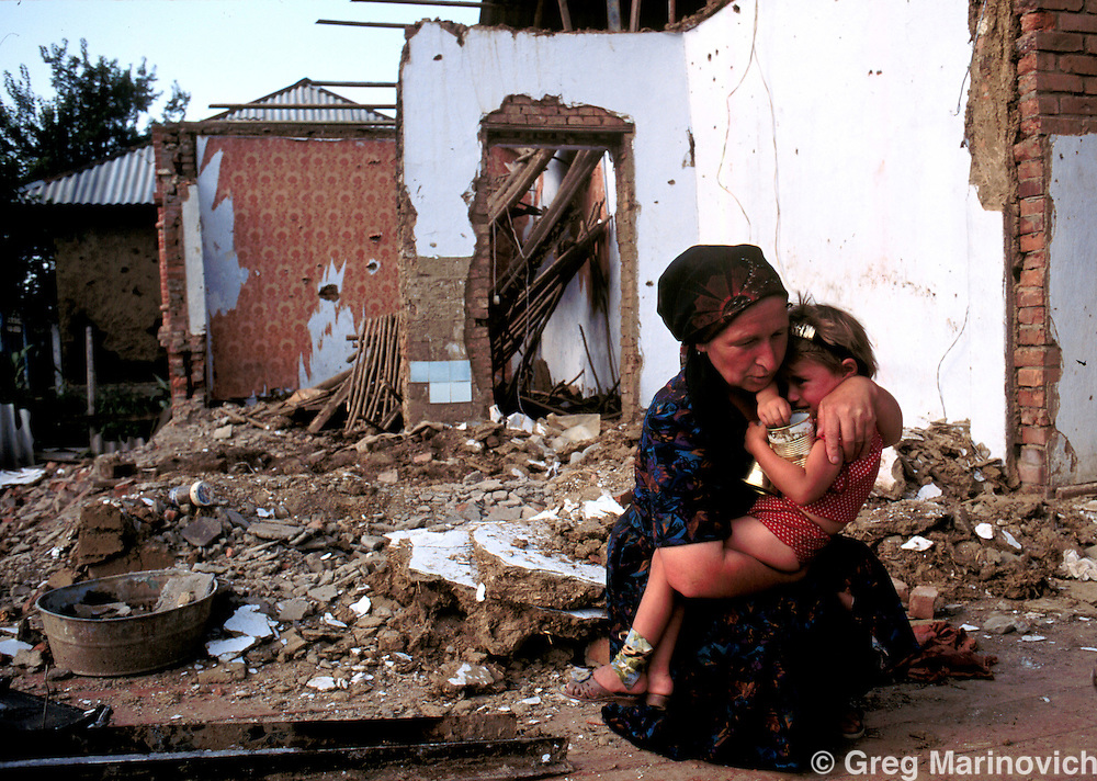 ISLAM MILITANT CHECHNYA JUL 1995: A Chechen woman comforts a child in their devestated home that was bombed by Russian forces in Serzenyurt village outside Grozny July 1995.  The Chechens are Moslem and have a strong sense of national identity.  Their fight for independence from Russia has increased an Islamic militancy and identity. (Photo by Greg Marinovich / Getty Images)